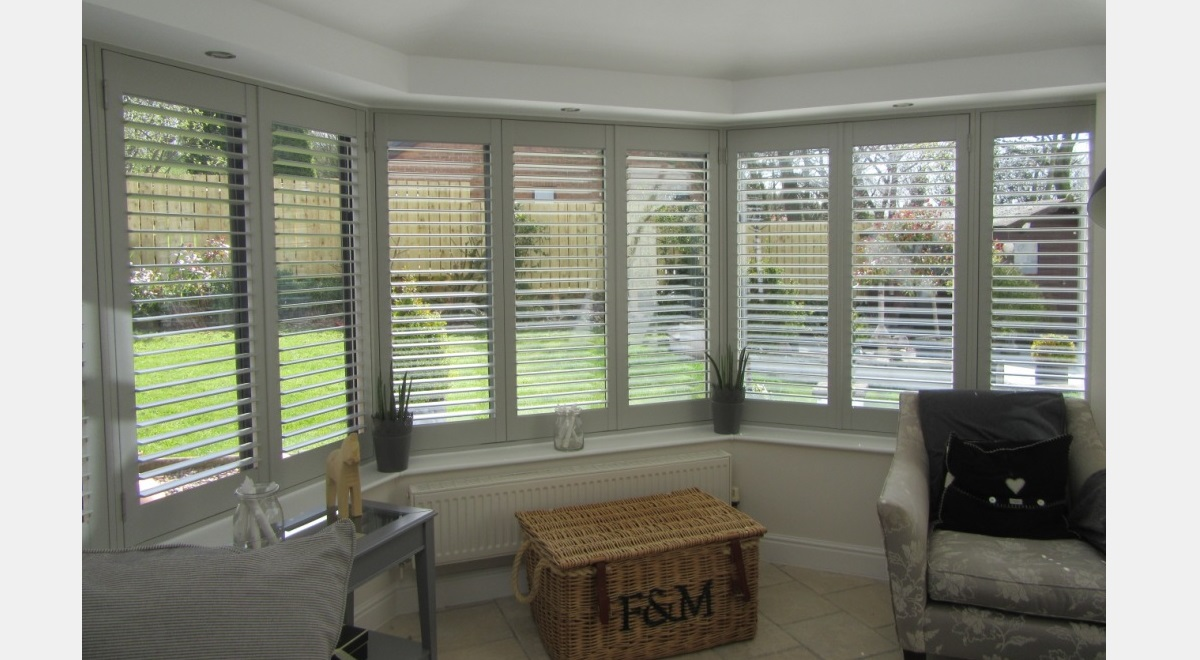 Full Height grey Hardwood Plantation Shutters in a large bay window