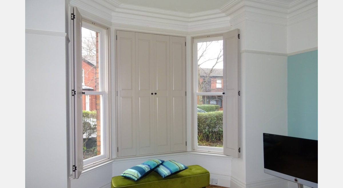 Full Height Hardwood Solid Shutters in a bay window
