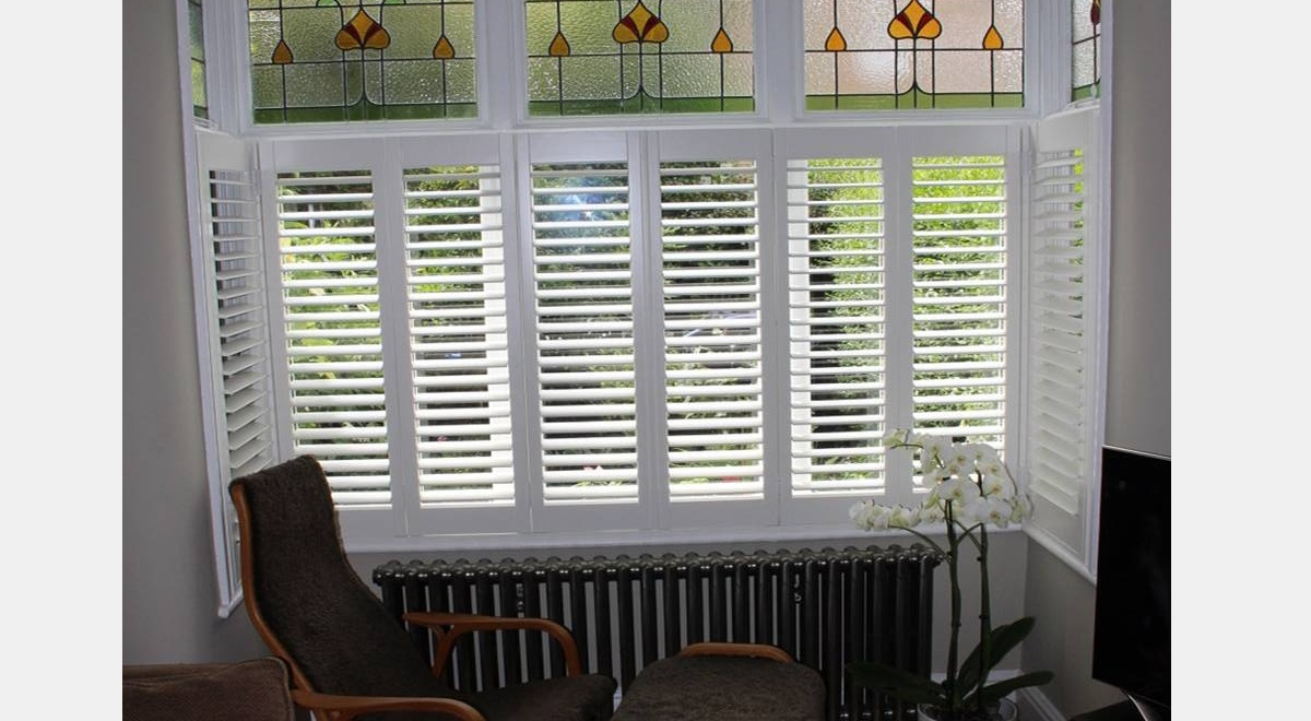Full Height white Hardwood Plantation Shutters in a box bay window