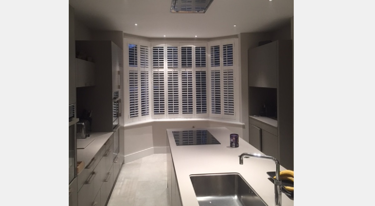 Full Height white Hardwood Plantation Shutters in a kitchen 3 section bay window