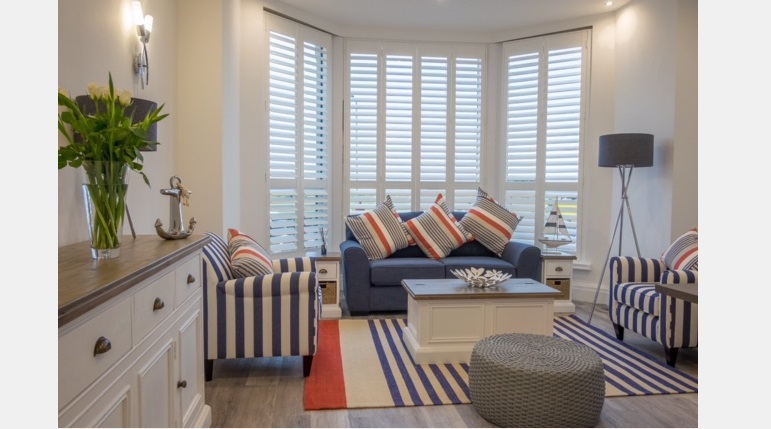 Full Height white Hardwood Plantation Shutters in a lounge bay window