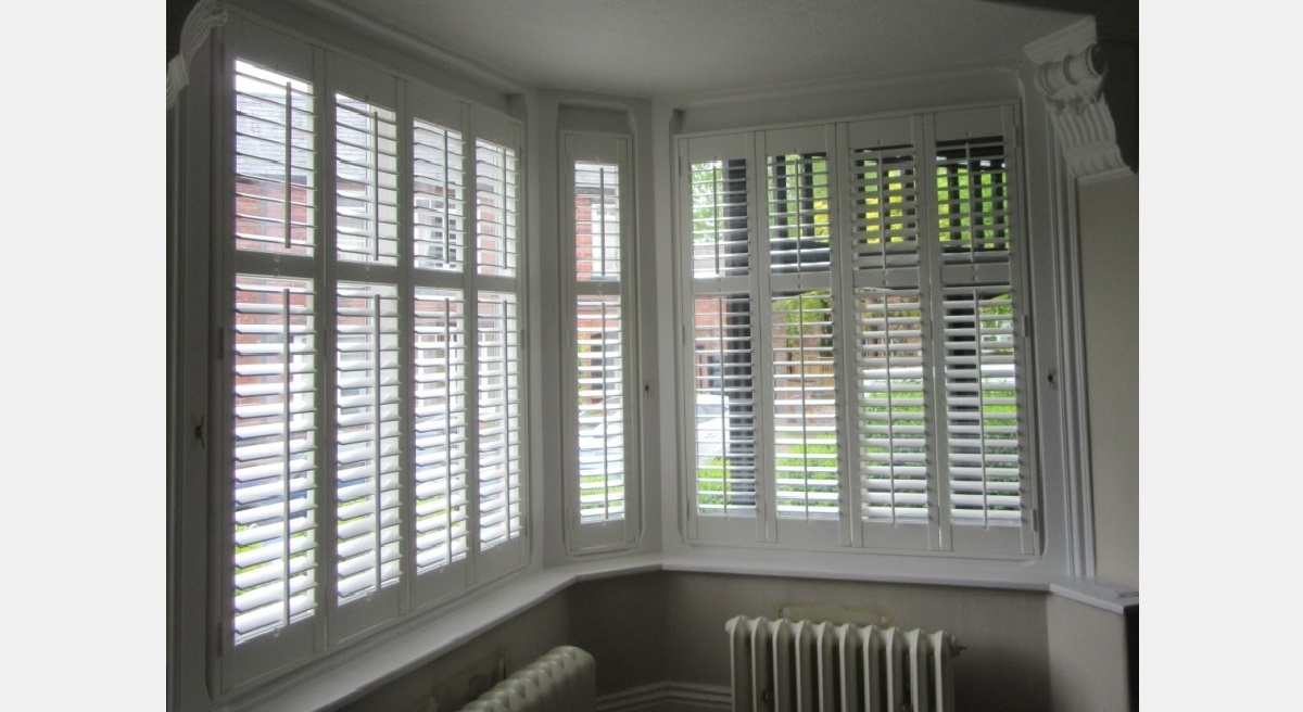 Full Height white Hardwood Plantation Shutters in a bay window