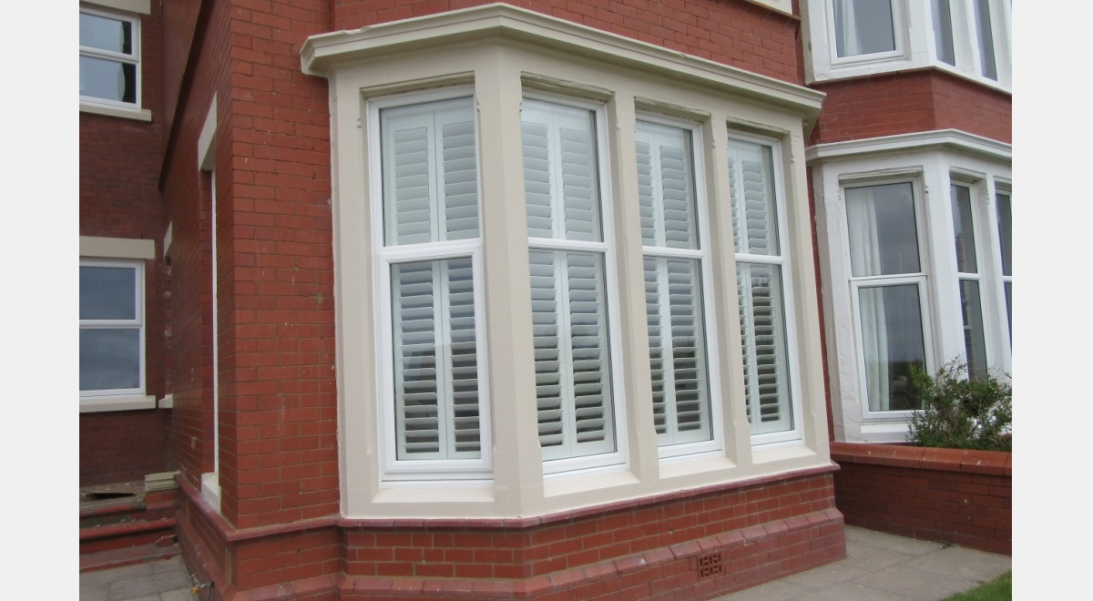 Full Height white Hardwood Plantation Shutters in a bay window from outside