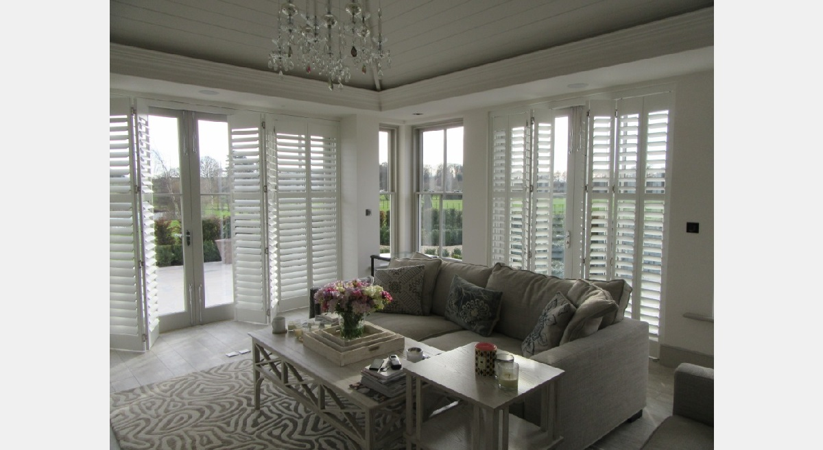 Full Height white Hardwood tracked Plantation Shutters in a lounge