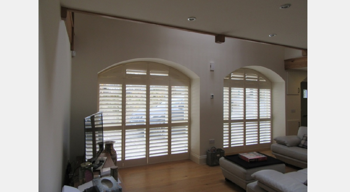 Hardwood Arched Plantation Shutters in lounge windows