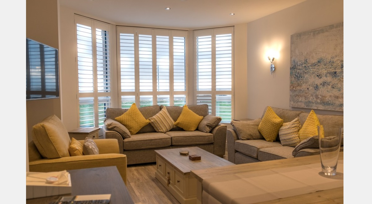 Full Height white Hardwood Plantation Shutters 3 section bay in lounge