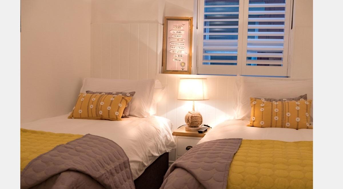 Full Height white Hardwood Plantation Shutters in spare bedroom