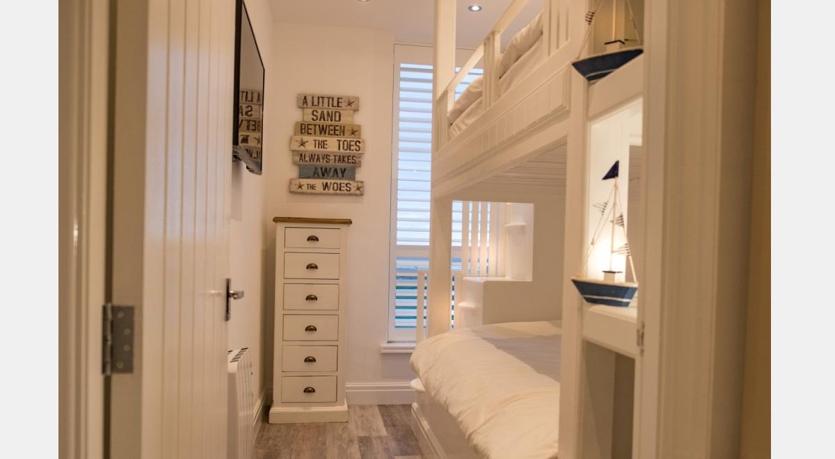 Full Height white Hardwood Plantation Shutters is childs bedroom