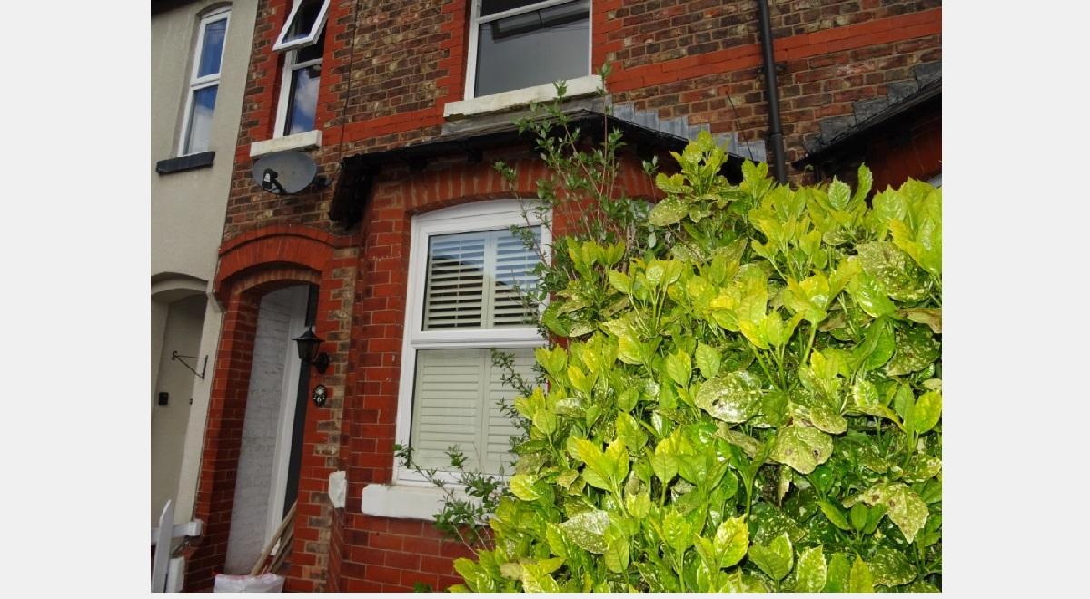 Full Height Hardwood Plantation Shutters in a 3 section bay window from outside with bush on right hand side